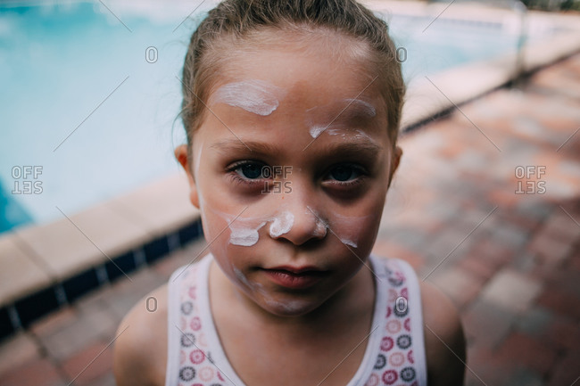Little girl with sunscreen on her face standing by a pool