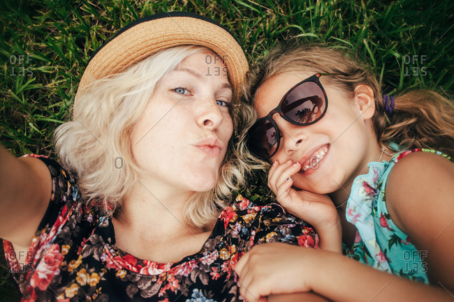 Mother and daughter lying in grass taking a selfie