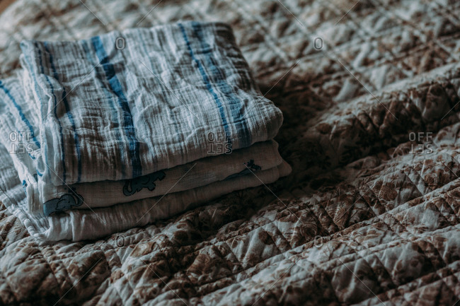 Baby blankets folded and stacked on a bed