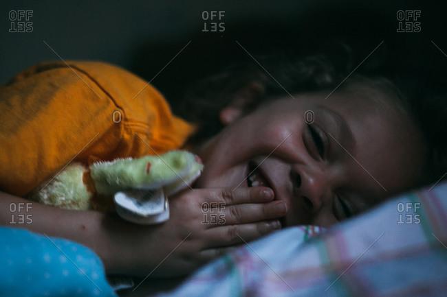 Little girl lying in bed giggling