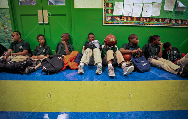 Washington D.C. - April 10, 2012: Students sitting against a wall waiting for recess at Stanton Elementary