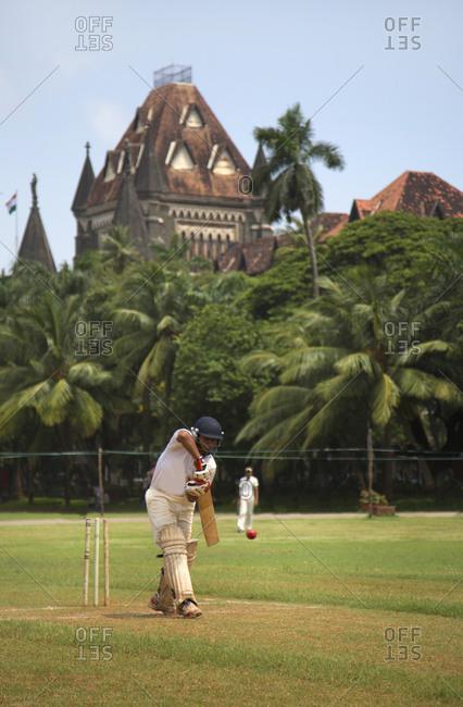 Mumbai, India - October 1, 2013: Young men playing cricket in Fort area of old town, Mumbai, India
