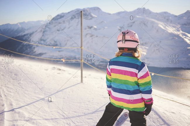 Girl in striped jacket and helmet stands at top of ski slope