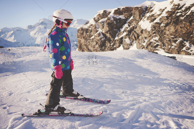 Young girl in skis at top of mountain