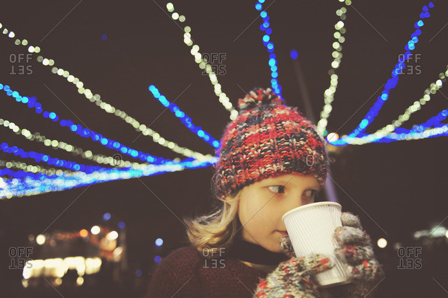 Young girl in knitted hat drinking warm beverage under strings of light at night