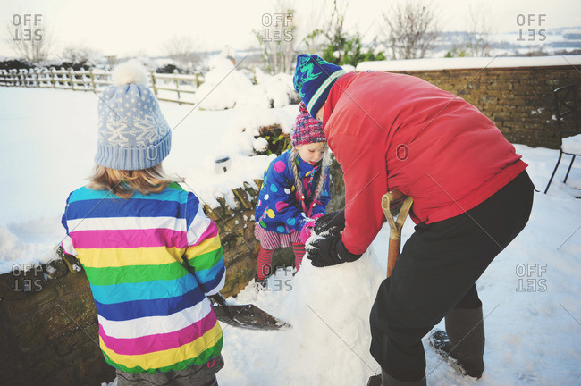 Man and two young girls building a snow sculpture