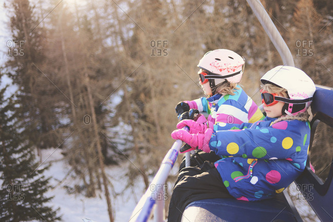 Two young girls in helmets and goggles ride a ski lift