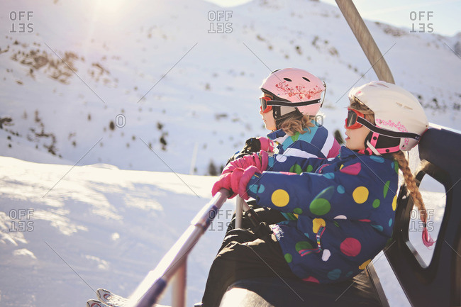 Pair of eager young skiers riding a chair lift