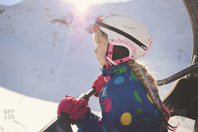 Side view of an eager young skier riding a chair lift