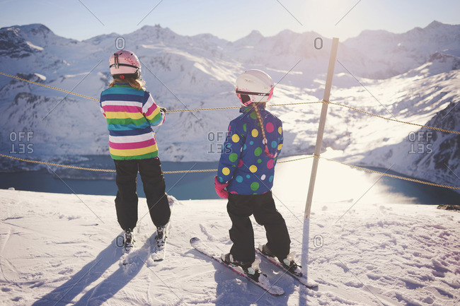 Two young girls overlook lake from top of ski slope
