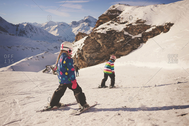Two young girls in brightly colored girl ski downhill