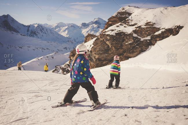 Two young children ski down ski slope