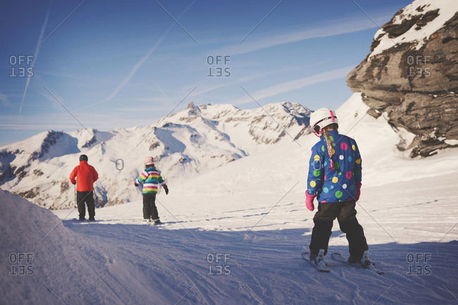 Man with two young girls ski past rocks on ski slope
