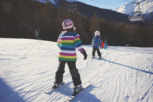 Two young girls ski on slope below chair lift