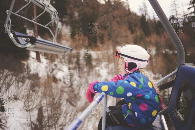 Young girl relaxes while riding on ski lift