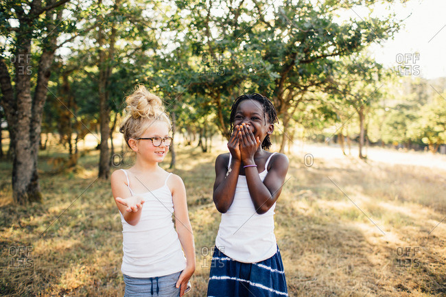 Two girls laughing together in wooded setting