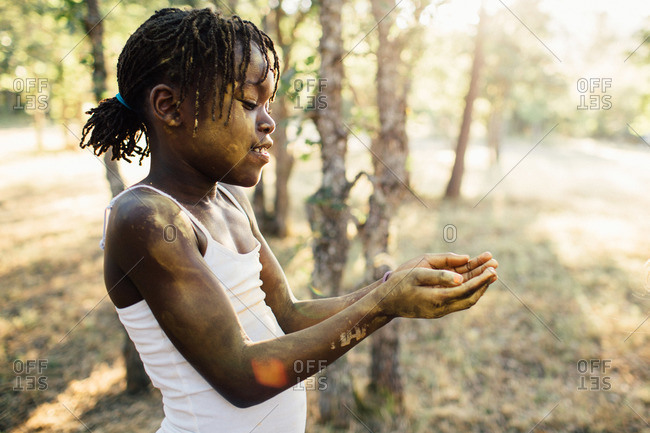Girl covered in yellow powder looking at hands