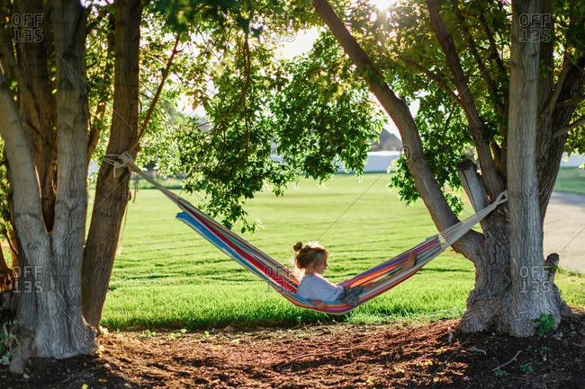 Girl lying in a hammock strung between trees