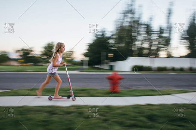 Girl on scooter zooming down sidewalk
