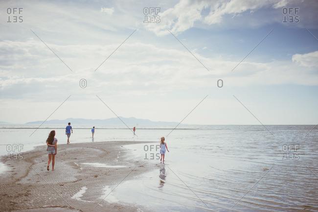 Kids walking on sandbar by ocean