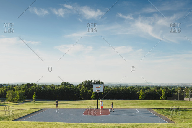 Kids playing in a basketball court in rural setting