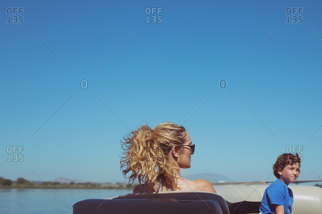 Woman and boy lounging in boat on lake