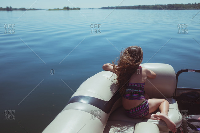 Girl lounging in a recreational boat on lake