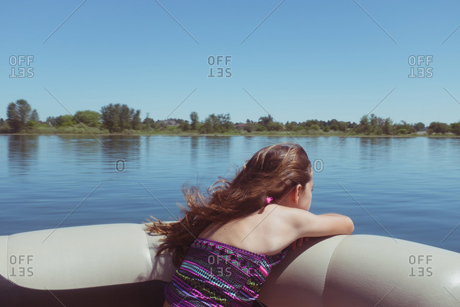 Girl lounging in recreational boat on lake