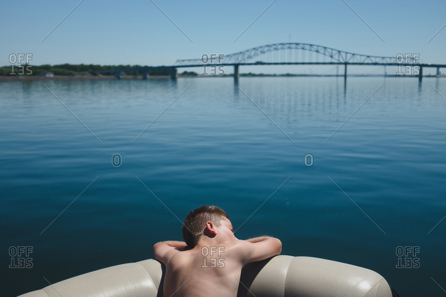 Boy resting in a recreational boat on lake