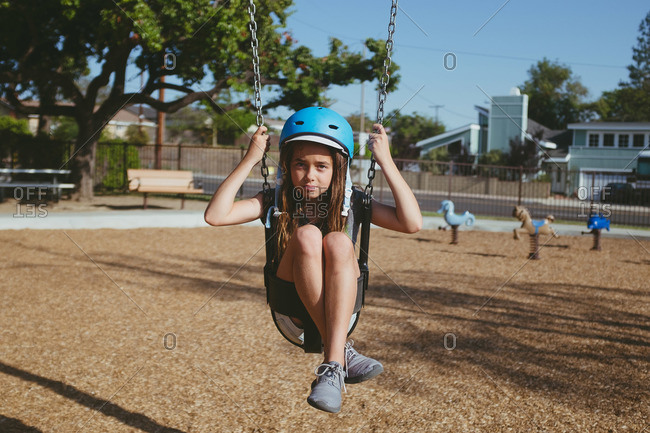 Girl wearing helmet sitting in baby swing