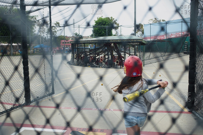 Girl swinging bat in batting cages