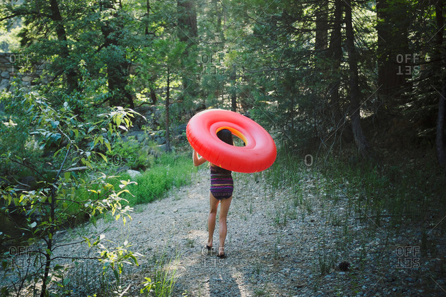 Girl carrying inflatable floatie in woods