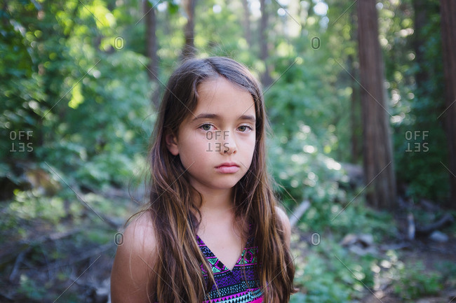 Portrait of serious girl standing in woods