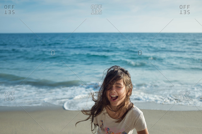 Girl laughing on a windy beach