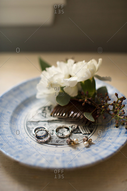 Wedding rings and a floral hair clip on a tray