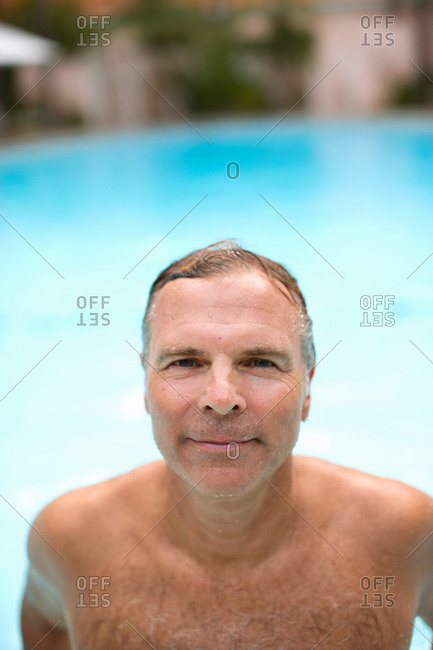A man emerges from a hotel pool