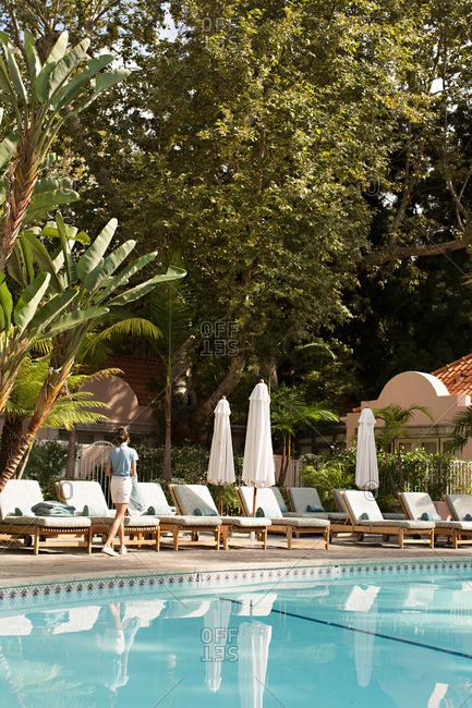 A pool attendant walks past a hotel pool