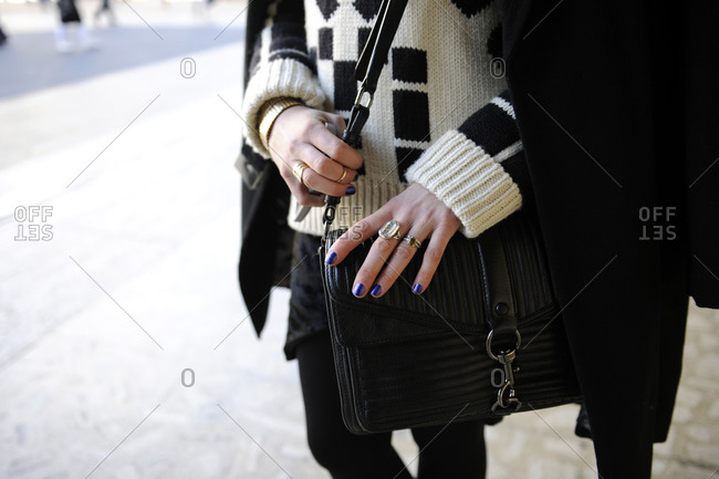 A woman in a black and white sweater with a leather purse