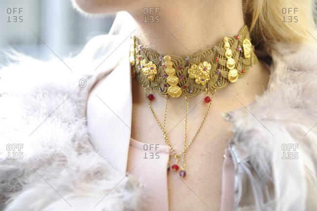 A woman wearing a delicate gold chocker