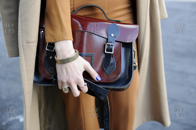 A woman holds a red and black satchel