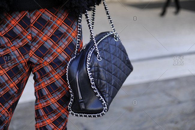 A woman in plaid pants and a quilted leather purse