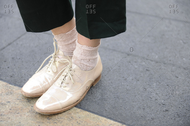 A woman wearing patent leather oxfords