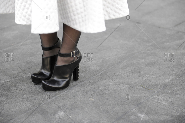 A woman in black leather heels