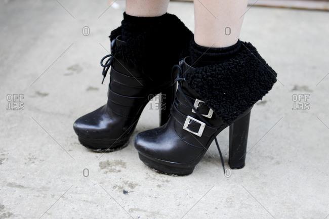 A woman wears high heeled booties