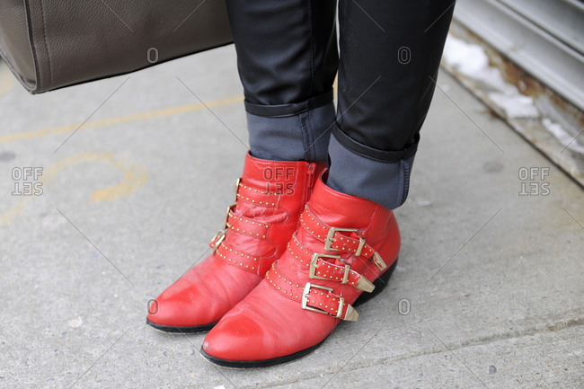 A woman in red shoes with gold straps