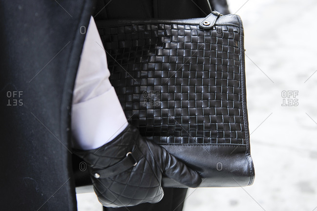 A woman in quilted gloves carries a woven handbag