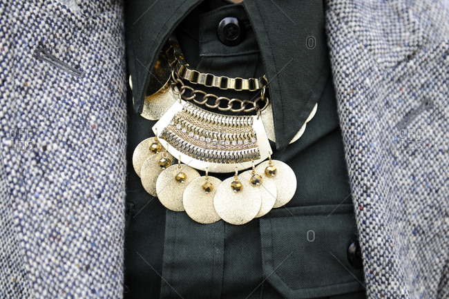 A woman wearing a gold necklace and a black cargo shirt