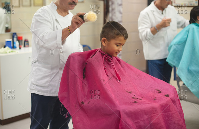 Young boy getting a haircut in barbershop