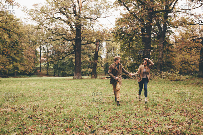 Young couple in love holding hands and running in an autumnal park