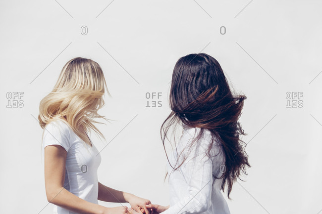 Two young women wearing white clothes tossing her hair in front of white background